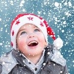 Happy child wearing Christmas hat looking at snow