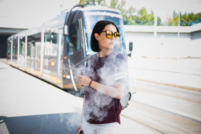 Stylish girl smoking an e-cigarette while standing near to road waiting for public transport