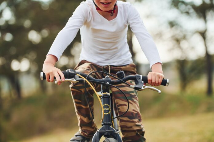Young boy riding his bike outdoors in the forest at daytime