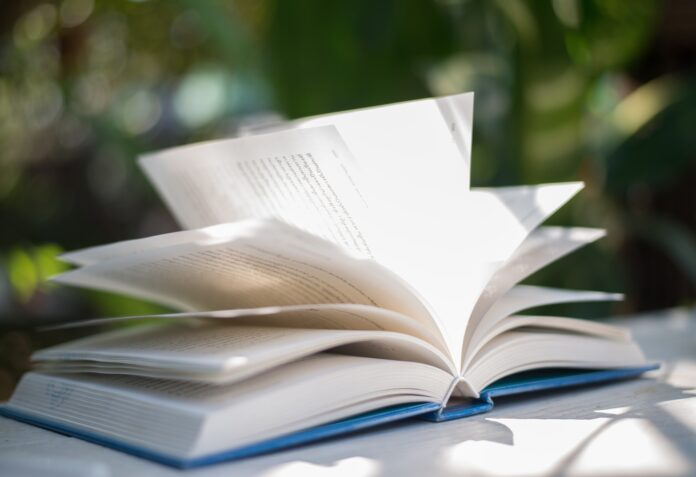 Close up of open book at home garden with nature bokeh background.