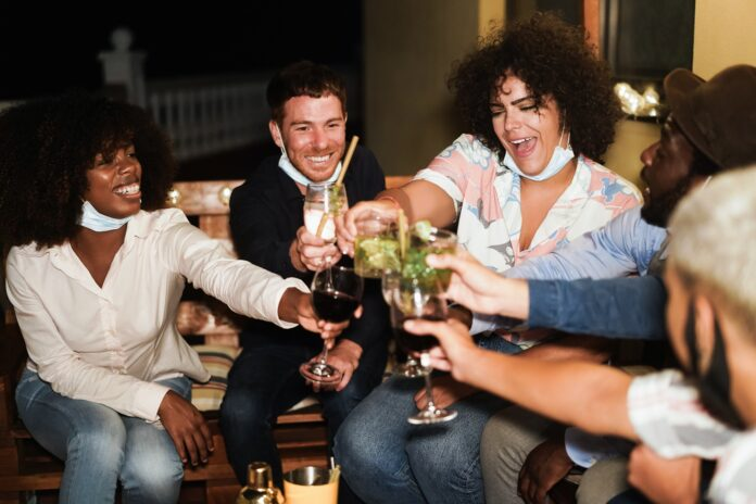 Happy multiracial people having fun drinking cocktails at terrace party during coronavirus outbreak